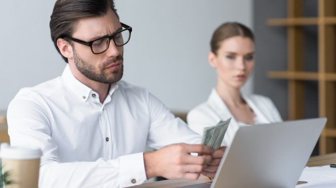 Serious Young Businessman Counting Cash While His Colleague Looking At Him Blurred On Background