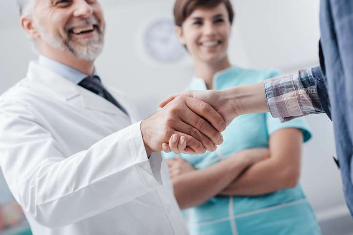 Medical Staff Welcoming A Patient At The Clinic: The Doctor Is Giving An Handshake And Smiling, Medical Service And Healthcare Professionals Concept, Hands Close Up
